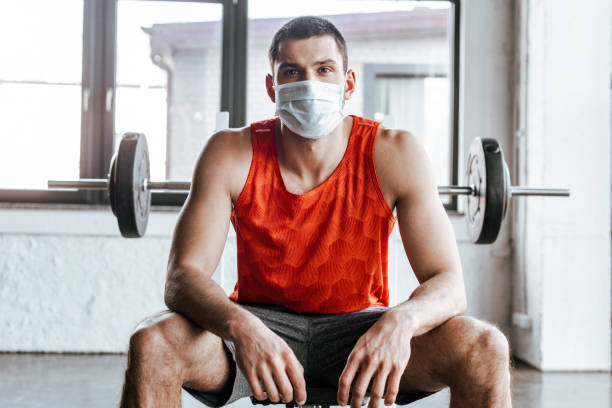 athletic sportsman in medical mask sitting near barbell in gym stock photo