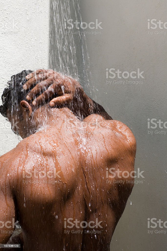 athletic, tanned  male back under the shower stock photo