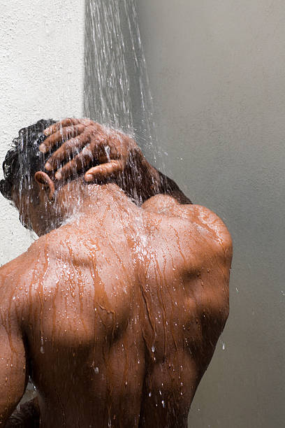 athletic gebräunten männlichen hinten unter der dusche - duschen stock-fotos und bilder