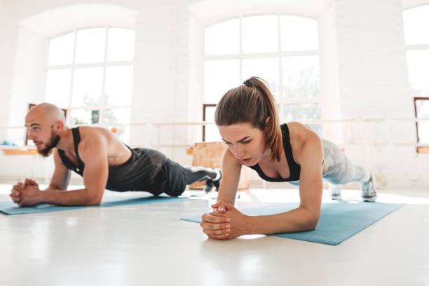 Athletische Frau und Mann, die Planke übung zusammen in weißen sonnigen Kaugummi. Fit junge Leute tun Planken-Training, um ihre Bauchmuskeln zu verbessern – Foto