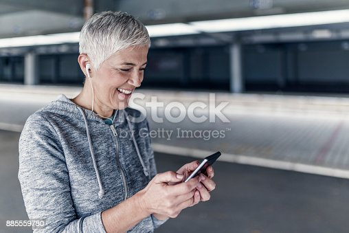 497687118istockphoto Athletic woman before start running setting up her smart phone app, fitness accessories 885559780