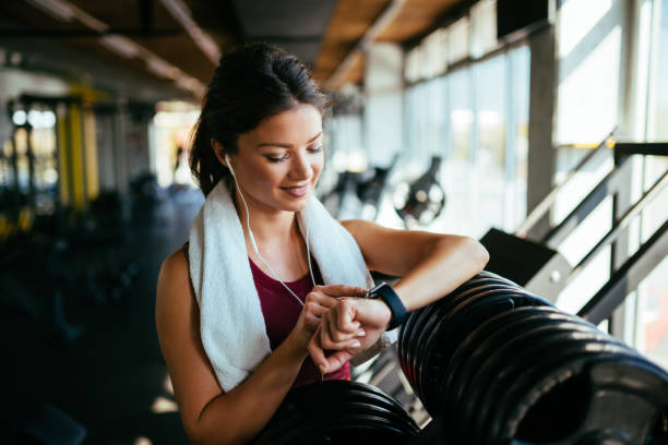 Athletic woman checking the time on wristwatch stock photo
