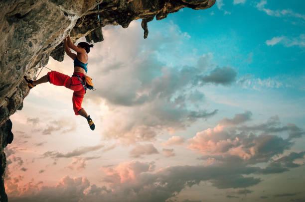 Mujer atlética subiendo sobre el acantilado de roca con fondo del cielo del amanecer - foto de stock