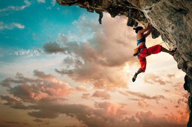 athletic woman climbing on overhanging cliff rock with sunset sky background - superare le avversità foto e immagini stock