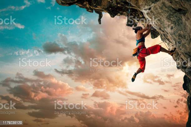 Photo of Athletic Woman climbing on overhanging cliff rock with sunset sky background