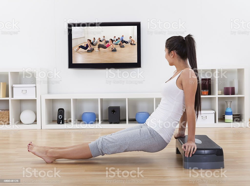 Athletic woman doing exercises in her livingroom royalty-free stock photo