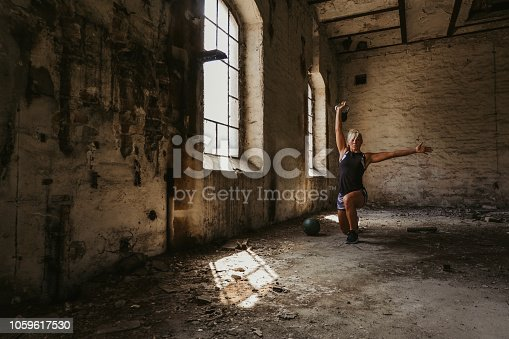 istock Athletic woman doing kettlebell lunge press in an old building 1059617530