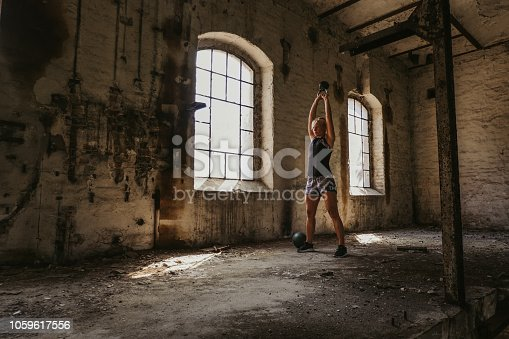 istock Athletic woman doing kettlebell swing in an old building 1059617556