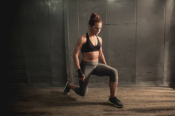 athletic woman doing lunges - lunge stock photos and pictures