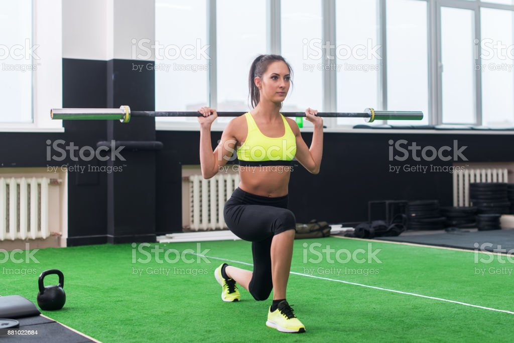 athletic woman doing lunges with barbell, working out legs and glute muscles stock photo