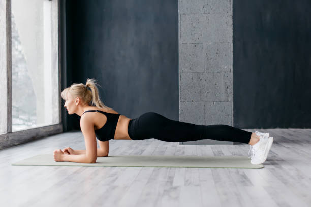 Athletic woman doing plank exercise in white sunny gum stock photo