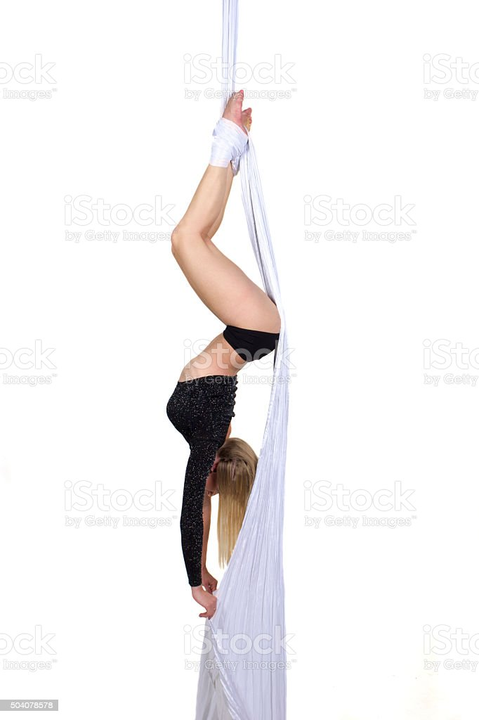 Athletic woman doing some tricks on silks stock photo