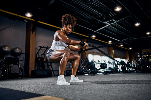 Motivated strong sporty lady performing the alternating waves exercise with battle ropes at the gym