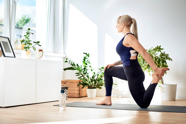 Athletic woman doing yoga, stretching exercise at home stock photo