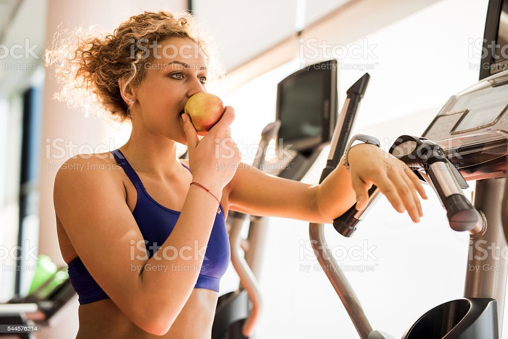 Athletic woman eating apple and in a gym. stock photo