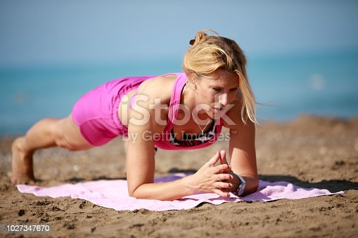 816941230istockphoto Athletic woman exercising on the beach 1027347670