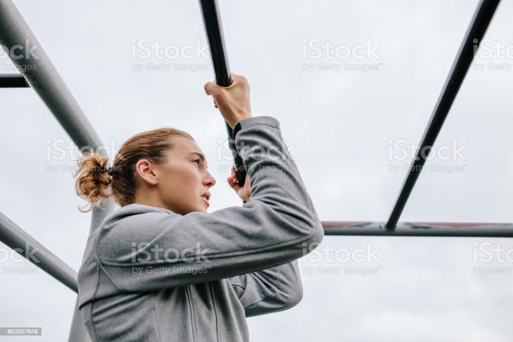 Athletic woman exercising outdoor on fitness equipments stock photo