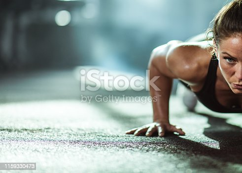 Young female athlete exercising push-ups with in a gym. Copy space.
