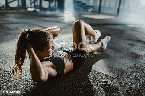 Young female athlete exercising sit-ups with hands behind her head in a gym.