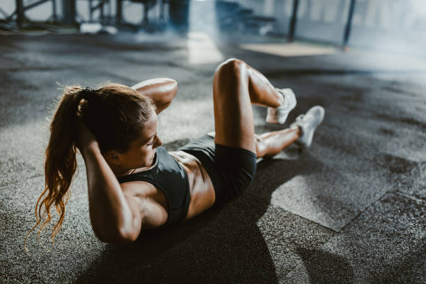 Athletic woman exercising sit-ups in a health club. Young female athlete exercising sit-ups with hands behind her head in a gym. abdominal muscle stock pictures, royalty-free photos & images
