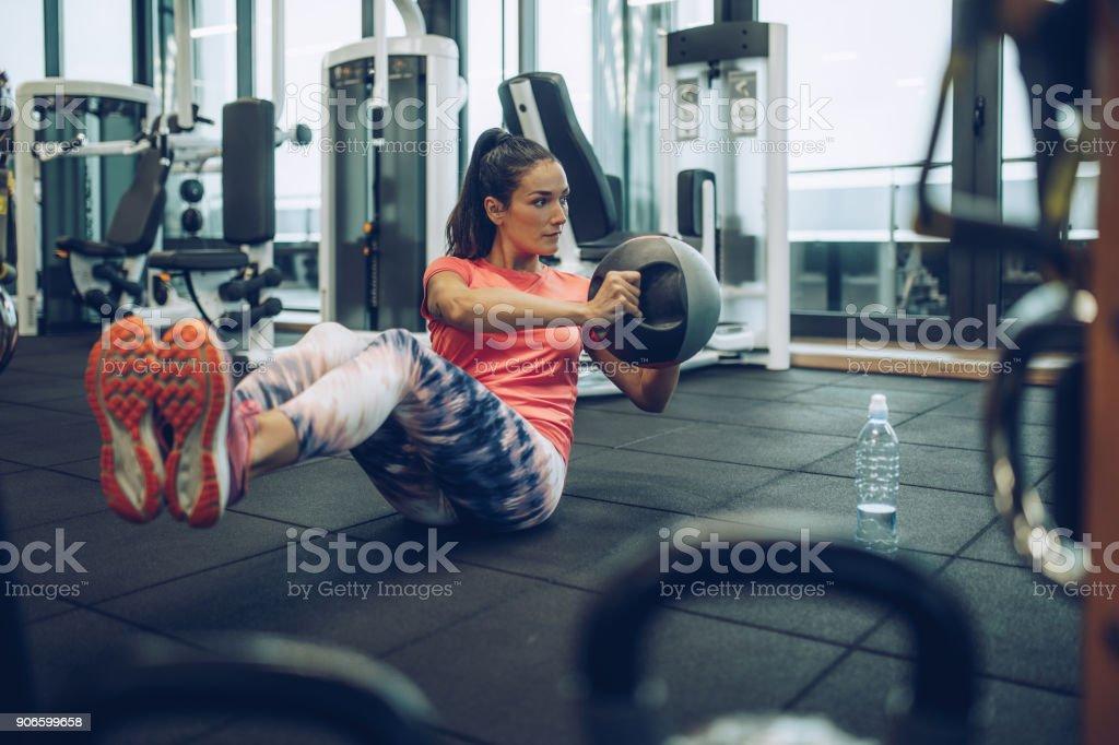 Sportliche Frau Sit-ups mit Medizinball in einen Health Club trainieren. – Foto