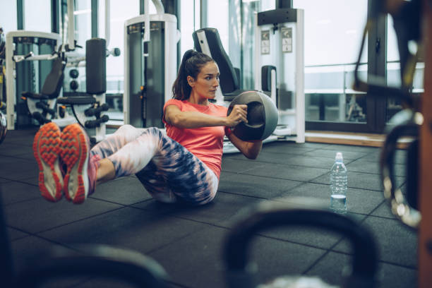 athletic woman exercising sit-ups with medicine ball in a health club. - sit ups stock photos and pictures