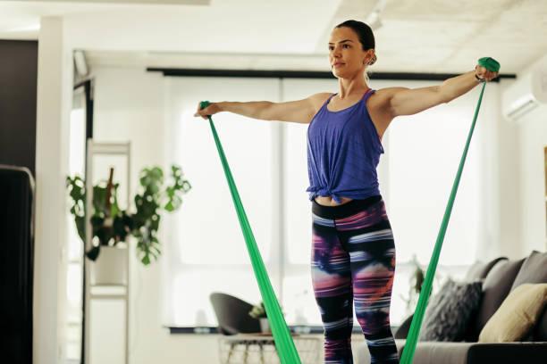 athletische frau trainiert mit einem powerband zu hause. - entspannungsübung stock-fotos und bilder