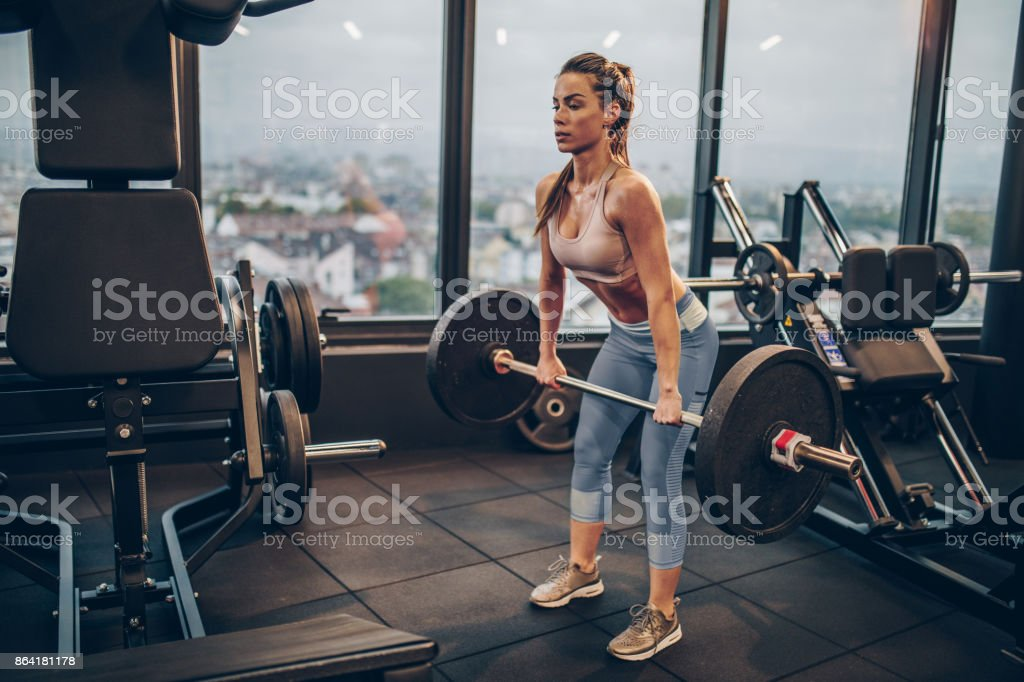 Athletic woman exercising with barbell in a health club. royalty-free stock photo