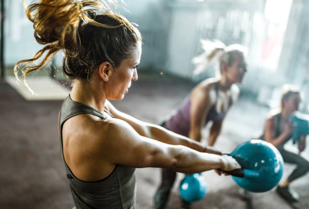 Athletic woman exercising with kettle bell on a class in a health club. stock photo