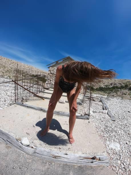 athletikerin flippt ihre haare vor verlassenem bootshaus - killer workouts stock-fotos und bilder