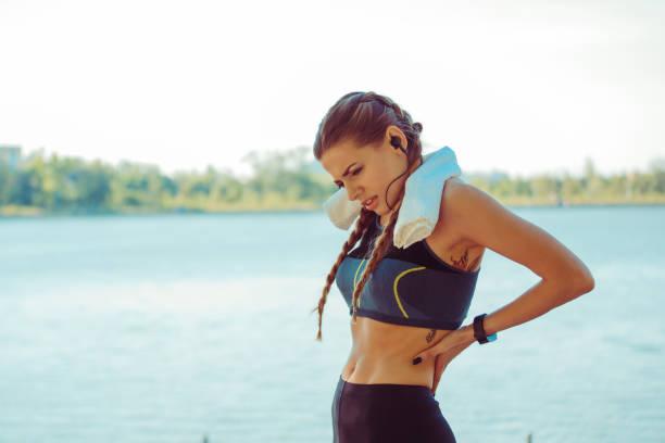 sportieve vrouw met rugklachten - atlete stockfoto's en -beelden