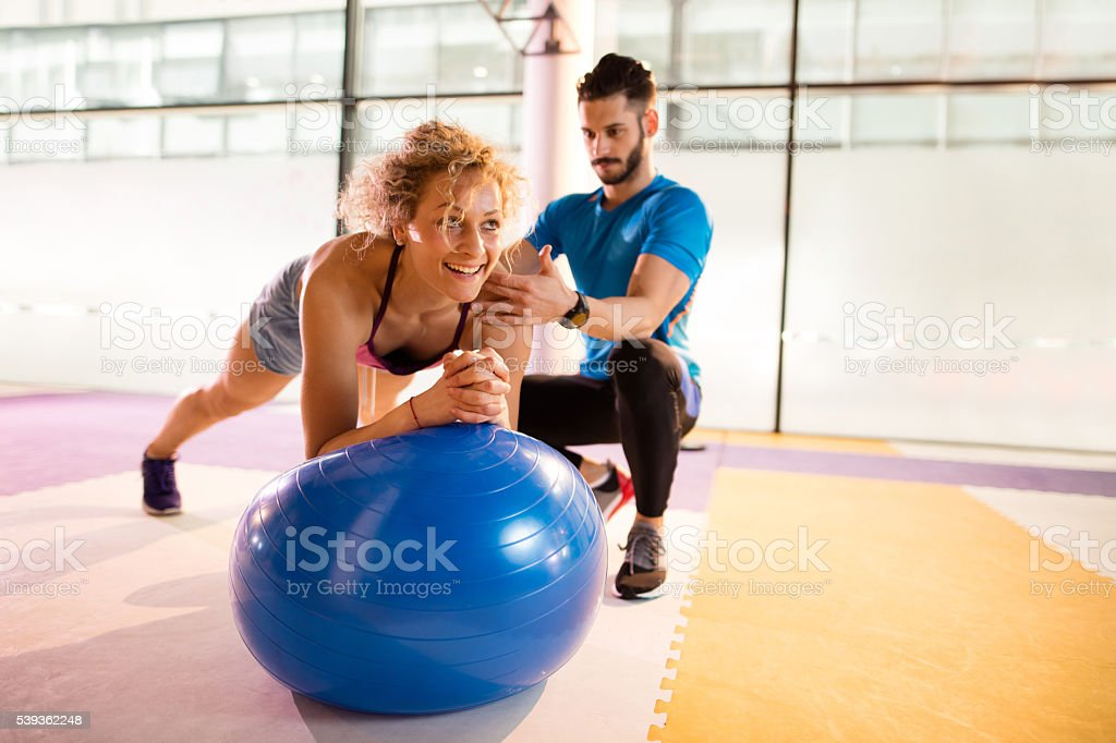 Athletic woman having Pilates training with fitness instructor. stock photo