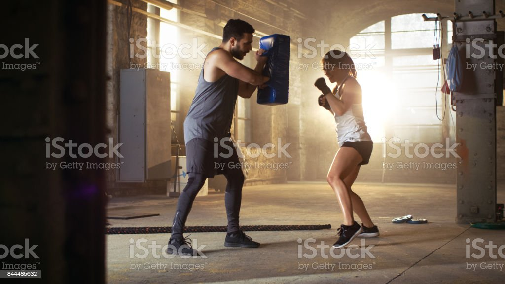 Athletic Woman Hits Punching Bag that Her Partner/ Trainer Holds. She's Professional Fighter and is Training in a Gym. royalty-free stock photo