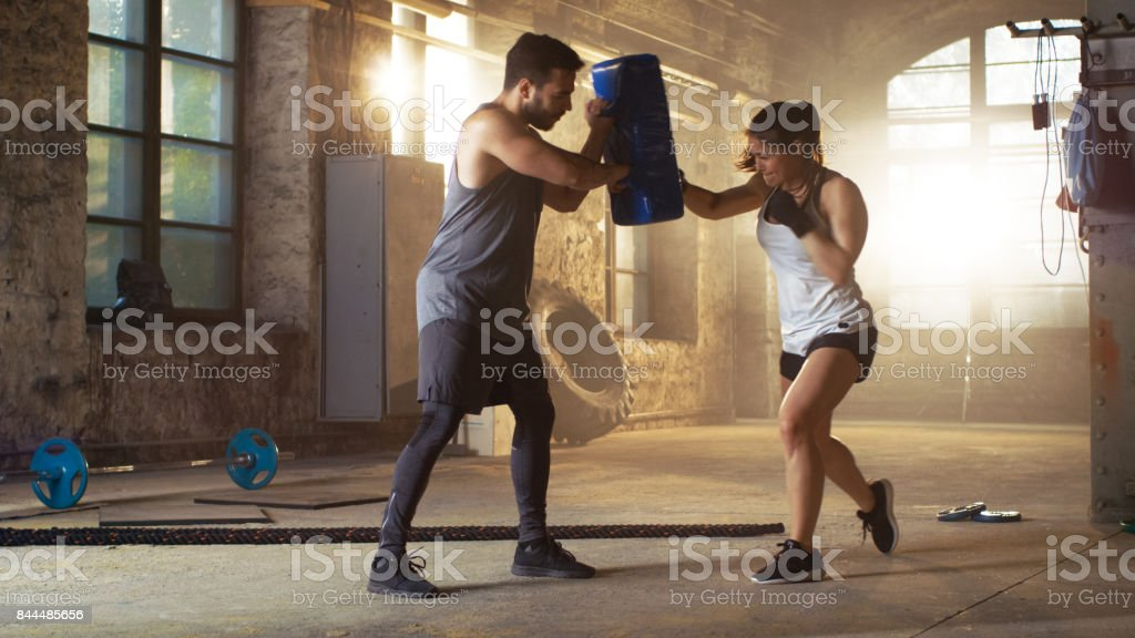 Athletic Woman Hits Punching Bag that Her Partner/ Trainer Holds. She's Professional Fighter and is Training in a Gym. stock photo