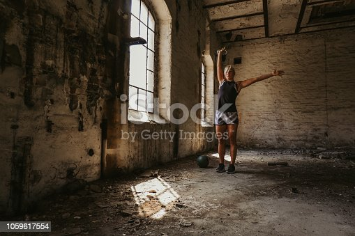 istock Athletic woman holding kettlebell up in an old building 1059617554