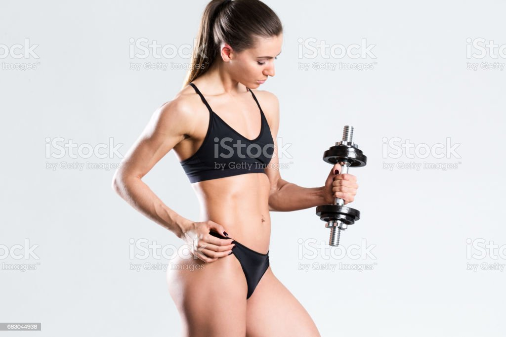 Athletic woman in black clothing with muscular body with dumbbell over gray background. foto de stock royalty-free