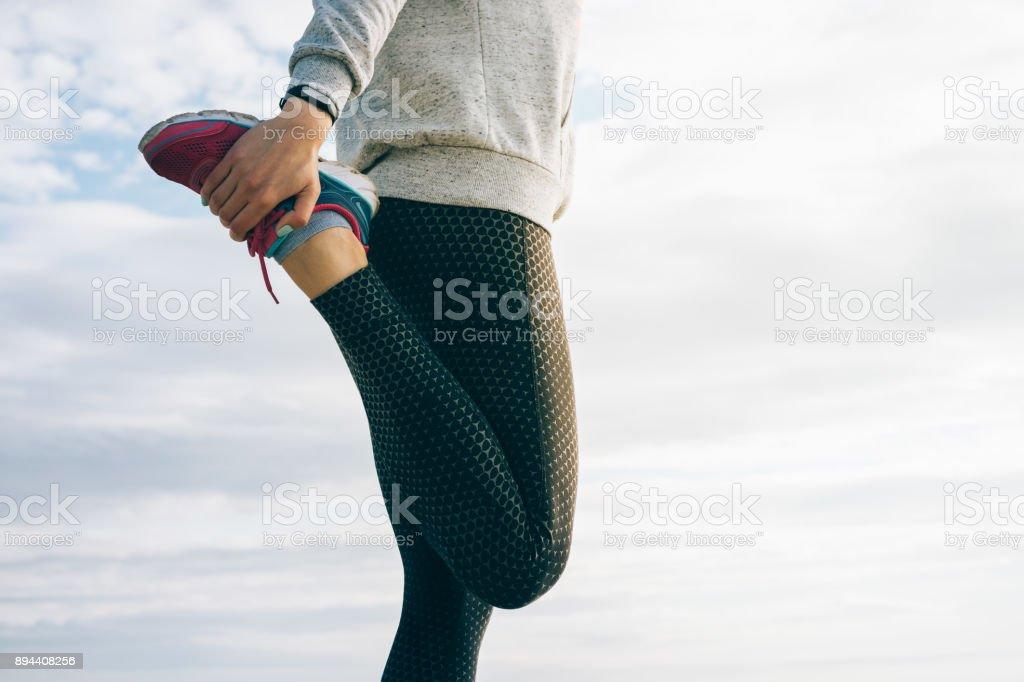 足のストレッチをしているスポーツウェアのアスレチック女 - アクティブライフスタイルのロイヤリティフリーストックフォト