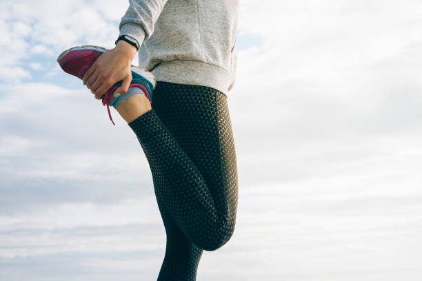 Athletic woman in sportswear doing stretching legs stock photo