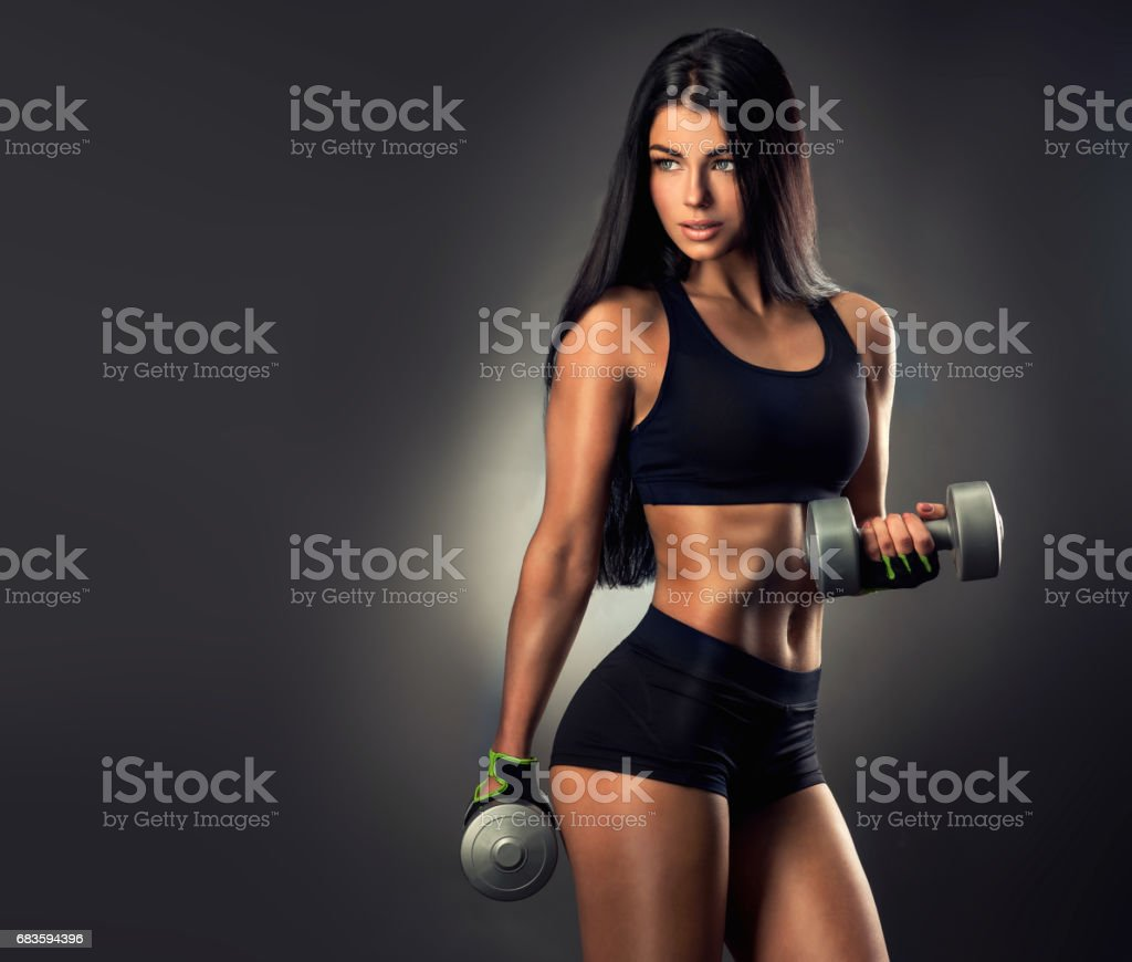 Athletic woman is pumping up muscles with dumbbells. stock photo