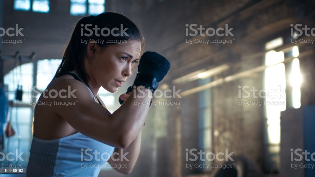 Athletic Woman is ready for Punch Punching Bag. She's Strong and Gorgeous Woman. They Workout in a Gym. stock photo