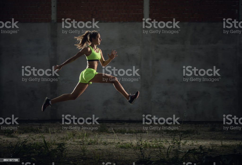 Athletic woman jumping in a run on sports training. royalty-free stock photo