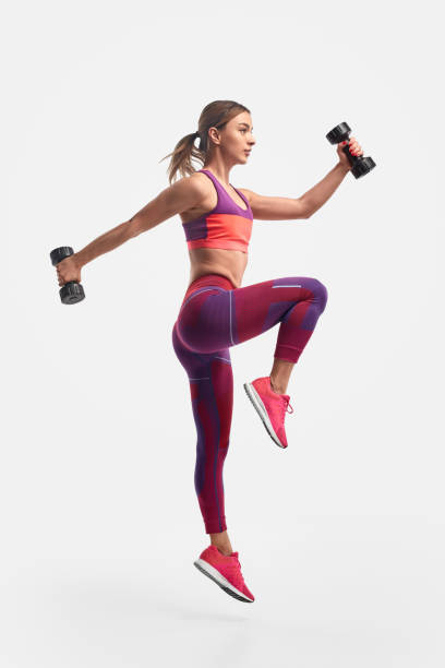 Athletic woman jumping with dumbbells stock photo