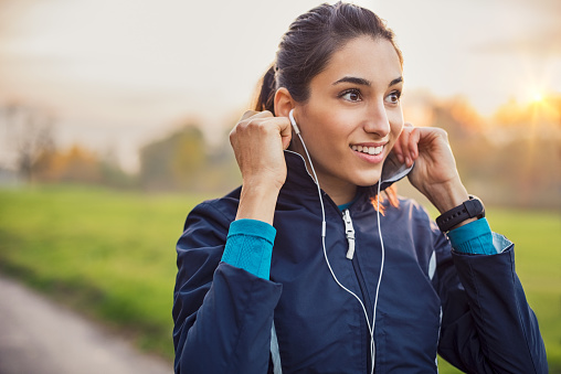 Young athlete adjusting jacket while listening to music at park. Smiling young woman feeling relaxed after a long run during the sunset. Happy sporty woman smiling and looking away during workout.