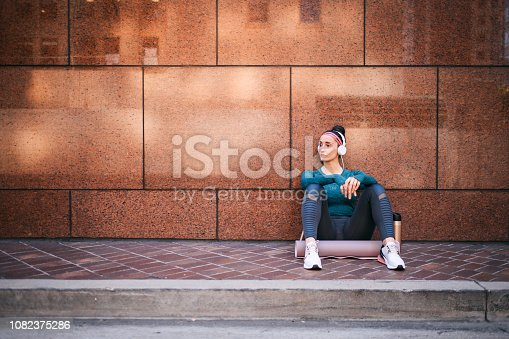 1091470492 istock photo Athletic woman listening to music while sitting with her back against a marble building wall in a city street 1082375286