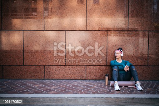 1091470492 istock photo Athletic woman listening to music while sitting with her back against a marble building wall in a city street 1091470502