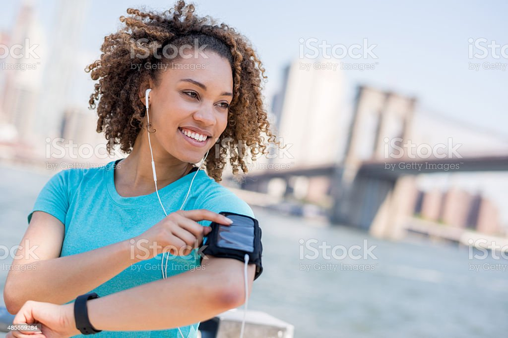 Athletic woman listening to music while working out outdoors stock photo