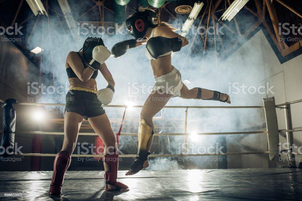 Atlética mulher fazendo um movimento de voo em uma luta de kickboxing com seu sócio económicas. - foto de acervo