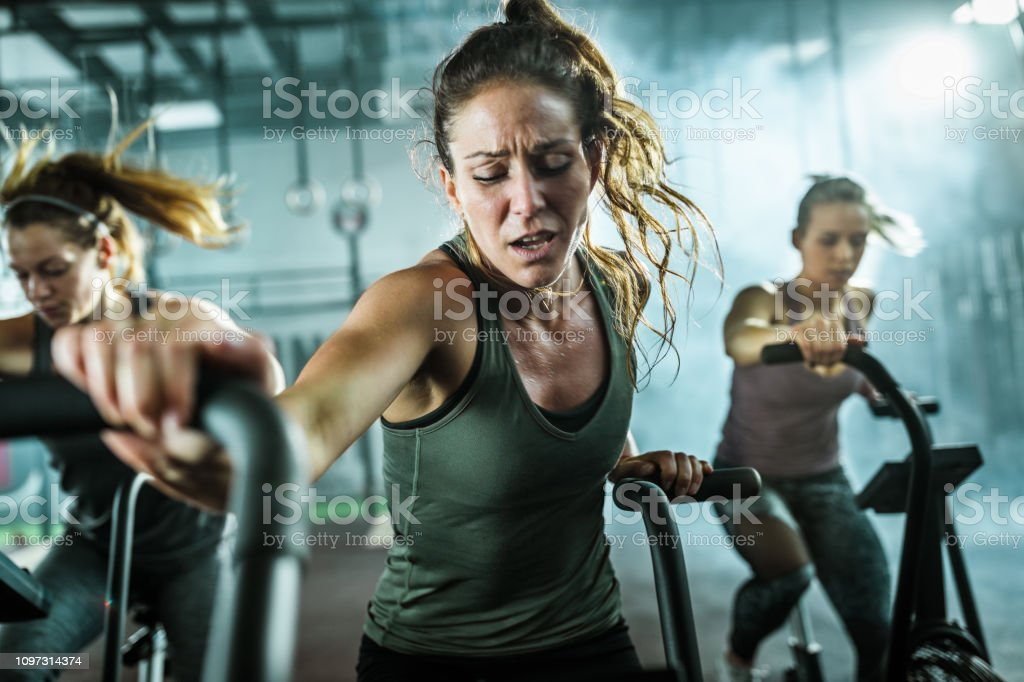 Young female athlete making an effort while having cross training on...
