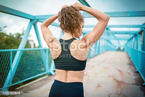 Back view of athletic woman making ponytail before sports training outdoors