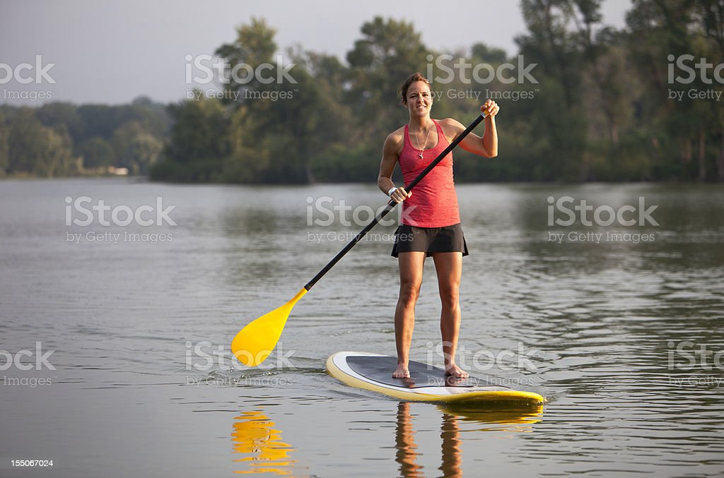 Athletic Woman Paddle Boarding on a Calm Midwestern Lake. royalty-free stock photo